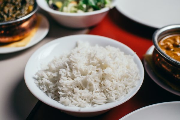 Rice in a white bowl with toppings in the background