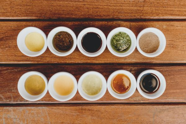 Ten sauces in little white bowls lined up in two rows on a wood table