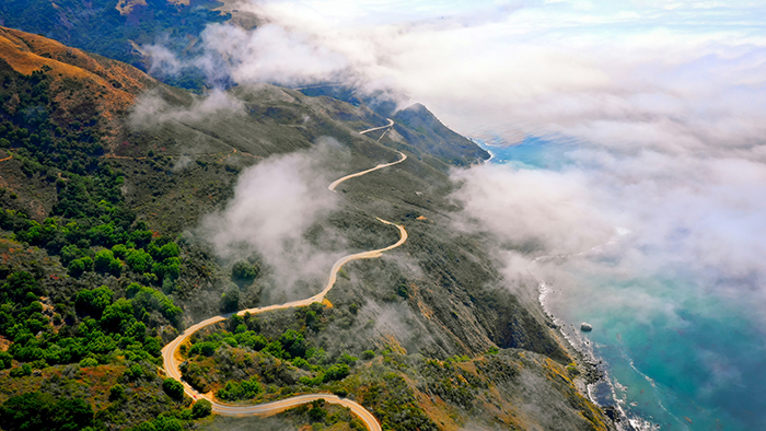 Sky view of road in the mountains near the ocean
