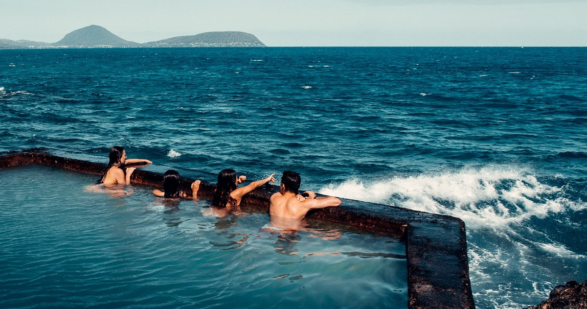 Four people swimming by the ocean