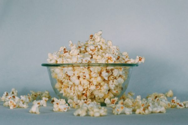 A glass bowl overflowing with popcorn