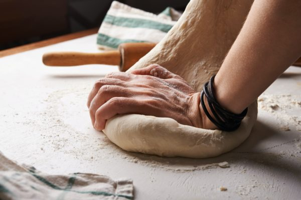 Hands kneading dough on counter