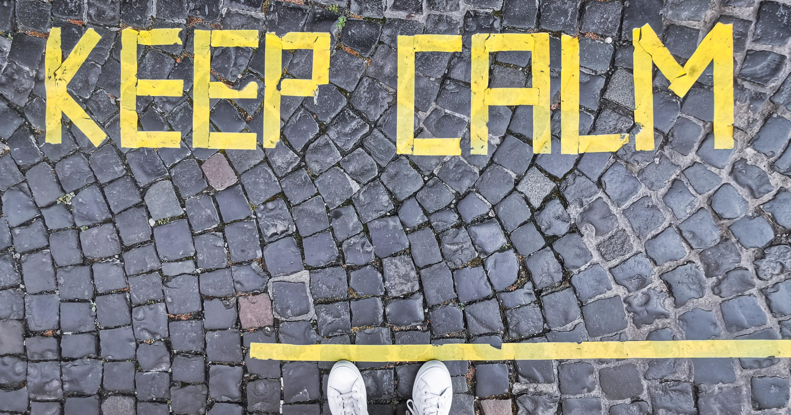 "Gray cobblestone path with the words ""Keep Calm"" in yellow"