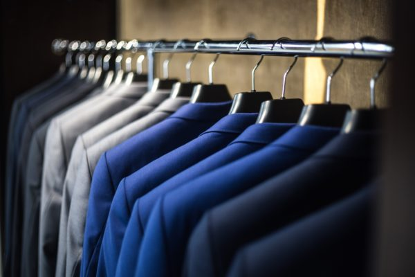Organized blue and gray suit coats on hangers in a closet