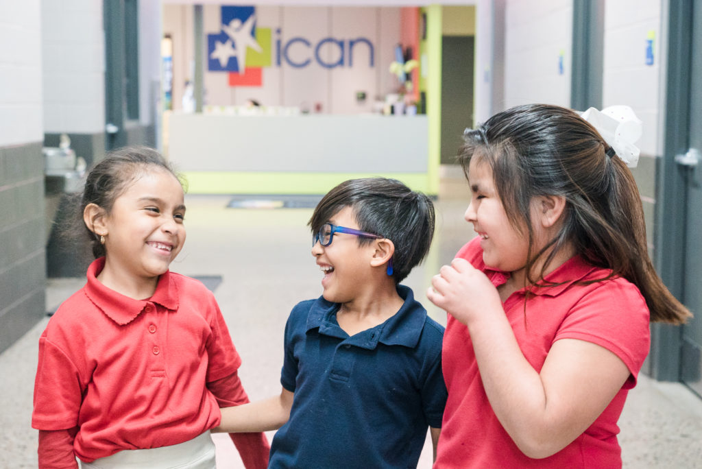 Three children laughing together at ICAN: Positive Programs for Youth