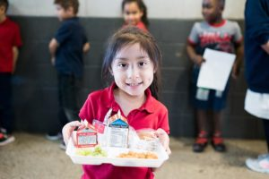 A young girl holding a tray with a balanced meal