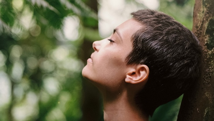 A person with short hair resting against a tree