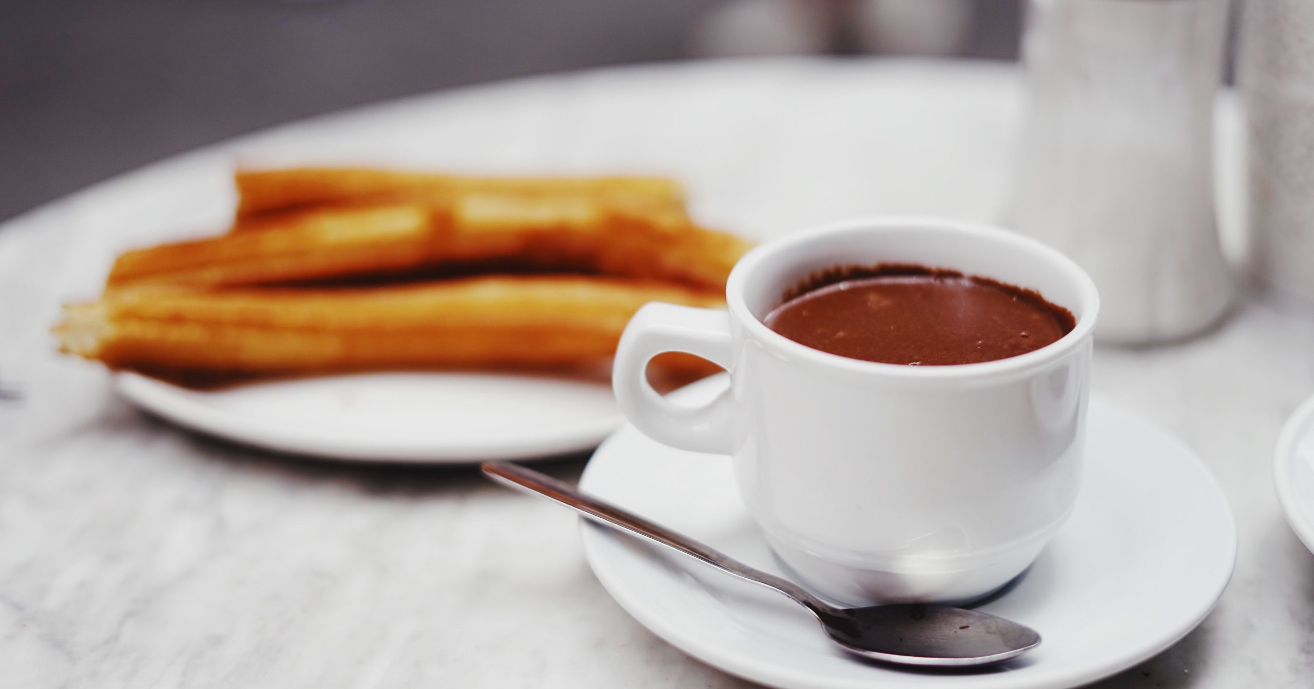 Churros on a white plate and chocolate sauce in a white mug