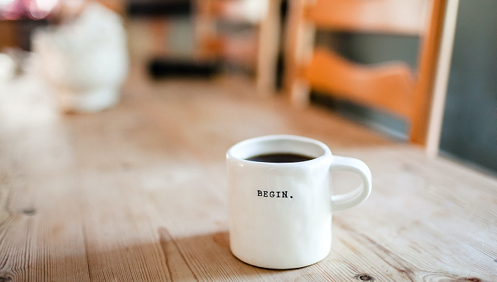 "A white coffee mug with the word ""begin"" on it"