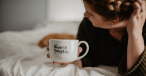 Woman lying in bed with a white coffee mug