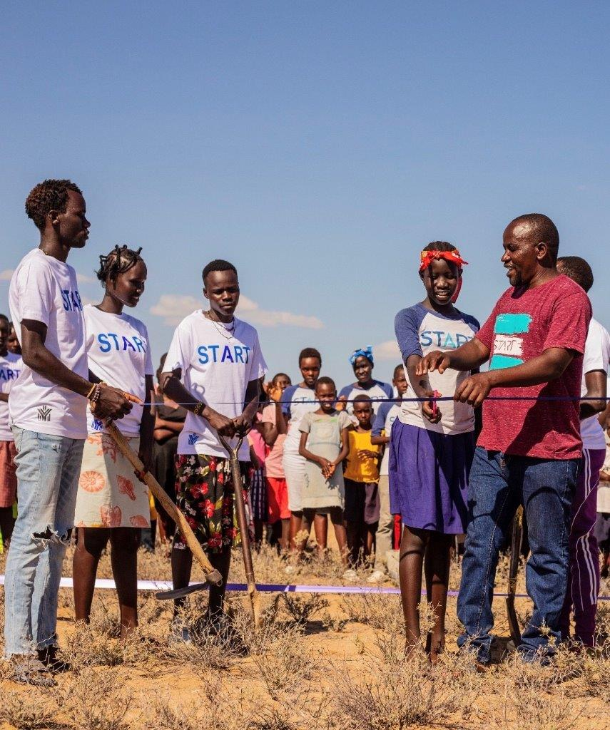 A group of people wearing START T-shirts and breaking ground on the transitional home in Kenya