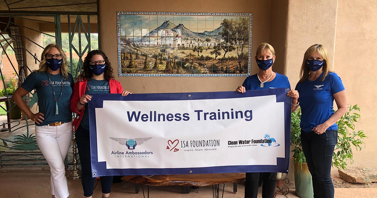 4 women holding a wellness training banner