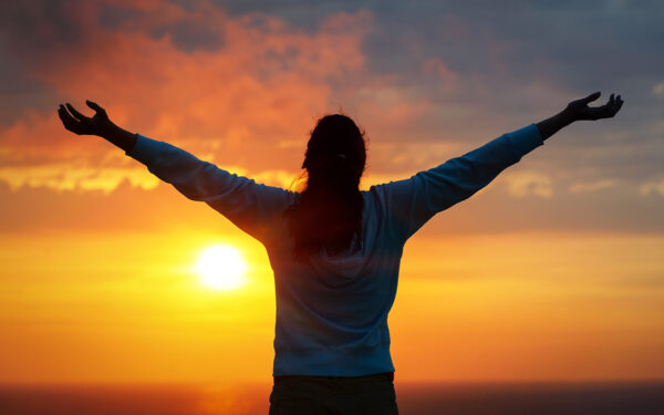 Silhouette of woman with raised arms against a sunset background