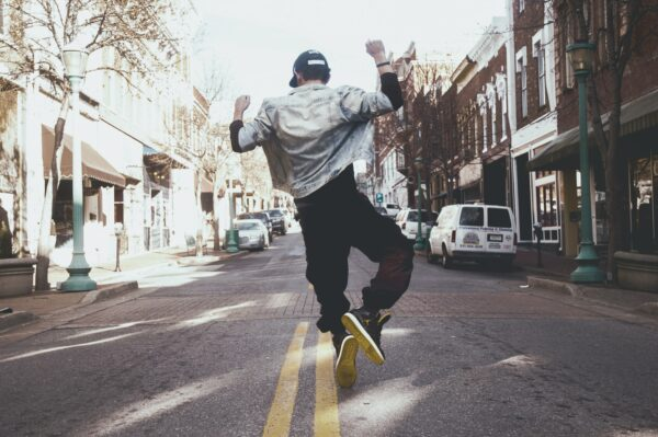 Guy jumping in the street with arms raised