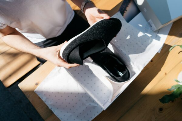 Overhead shot of woman unboxing black slip-on shoes