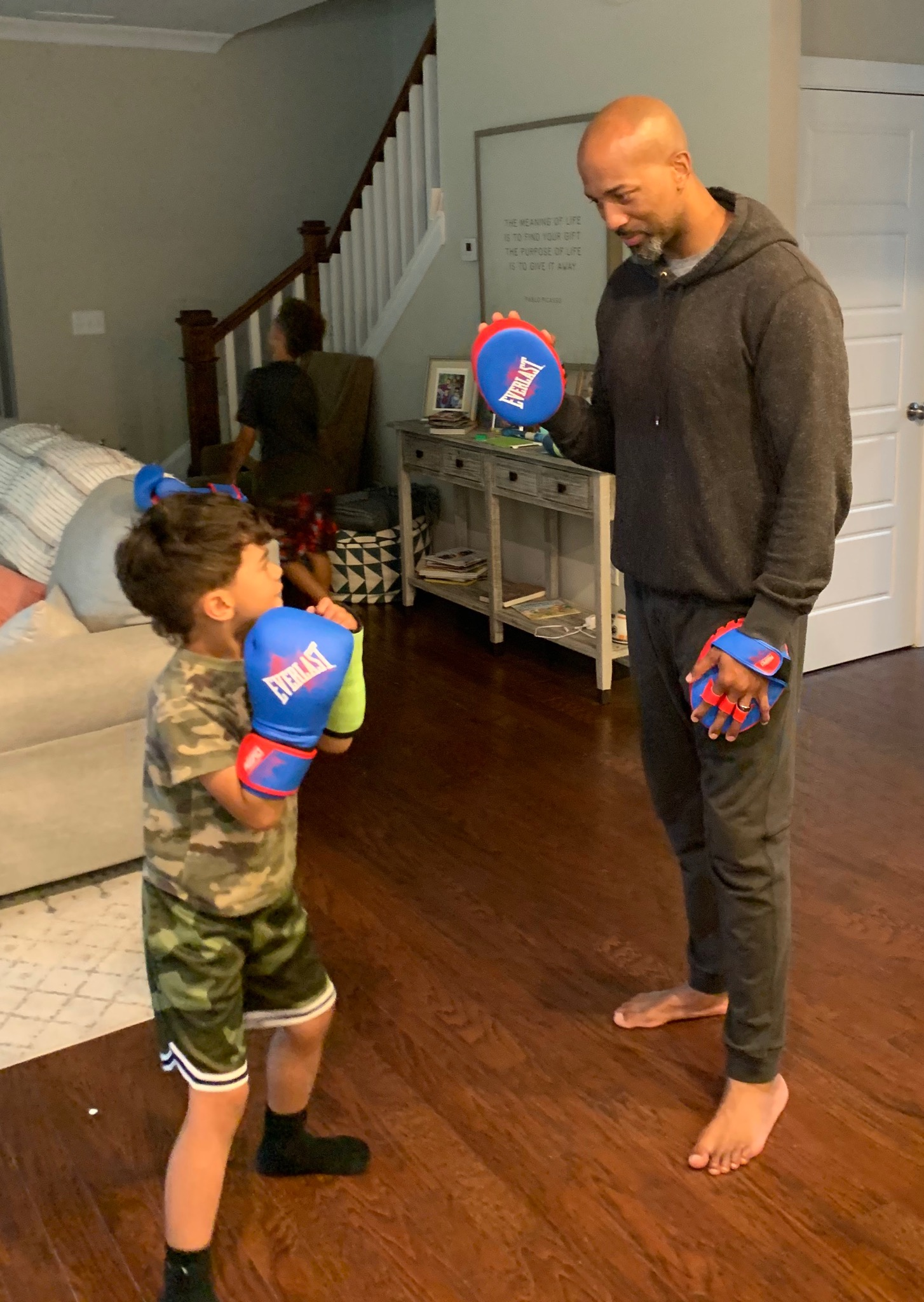 Charles Payne and his son boxing in the living room