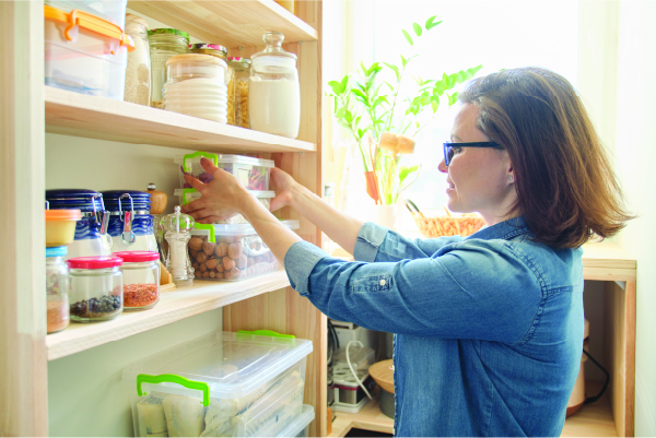 Woman arranging reusable food storage containers on a wooden pantry shelf