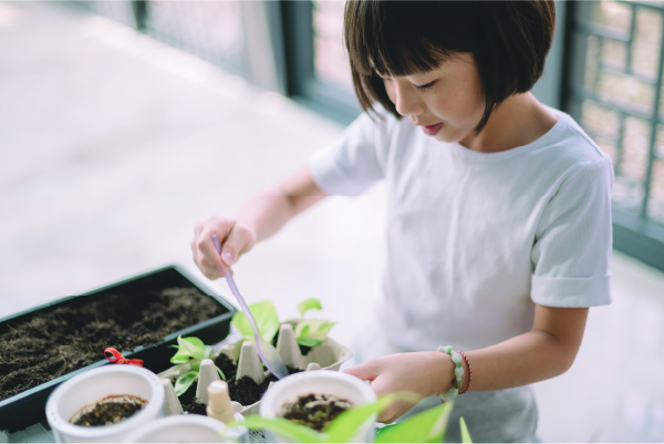 A child scooping dirt into a planter with a spoon