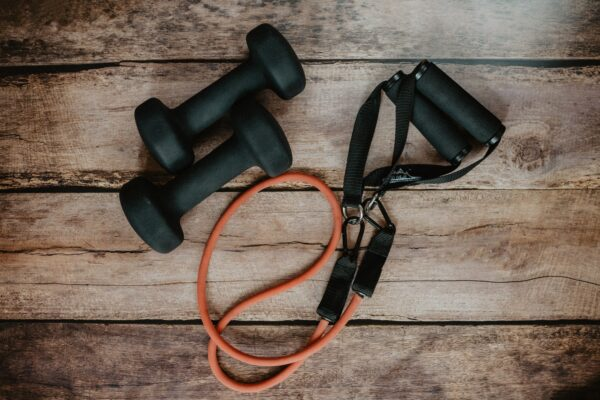 Two dumbbells and a resistance band on a wooden background