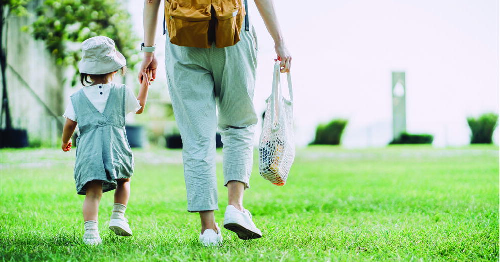Parent holding hands with their child while walking on the grass and carrying a reusable bag