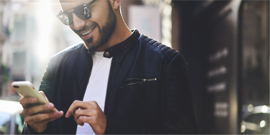 Man in sunglasses smiling and using smartphone