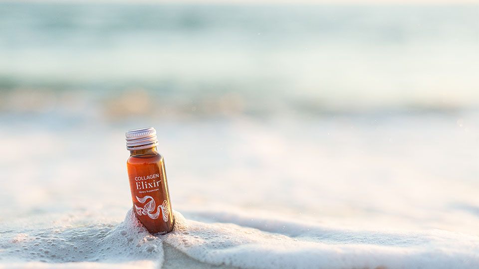 Isagenix Collagen Elixir bottle in the sand on the beach