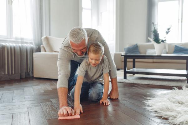 A man and a boy scrubbing the floor