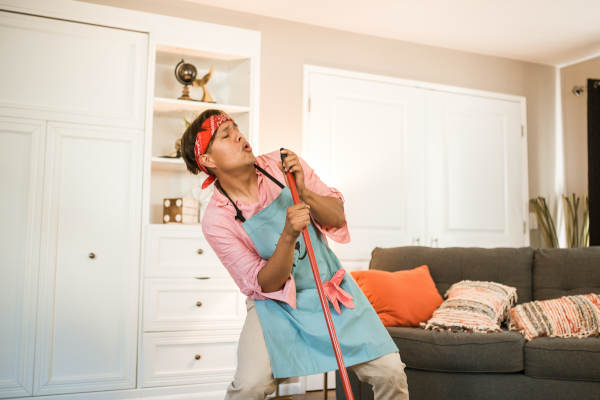 Man singing into broom handle while cleaning