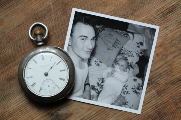Pocket watch and black-and-white photo of father holding a baby