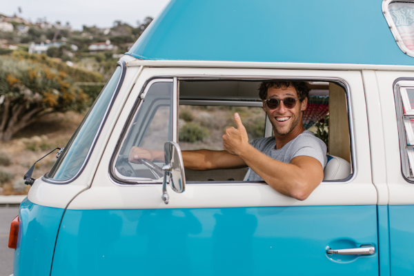 Man in sunglasses giving a thumbs up while driving a bright blue van