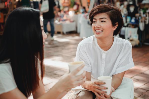 Two women enjoying coffee outside