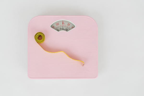 Light pink analog scale with a yellow tape measure on top