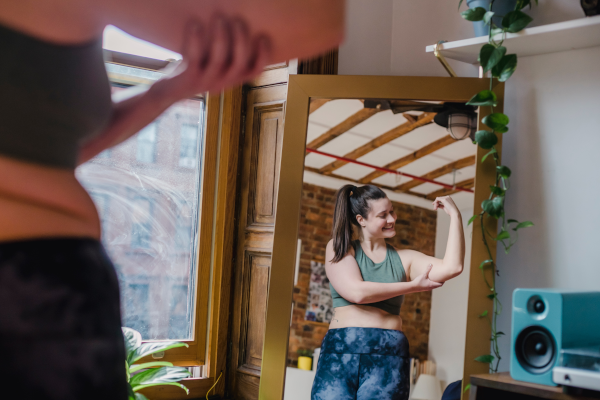 Woman flexing bicep in the mirror