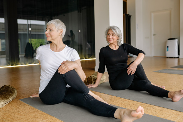 Two older women stretching on yoga mats